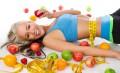 mujer en el suelo rodeada de frutas con cinta métrica rodeando la cintura