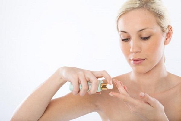 Chica aplicándose una pequeña cantidad de sérum en un dedo